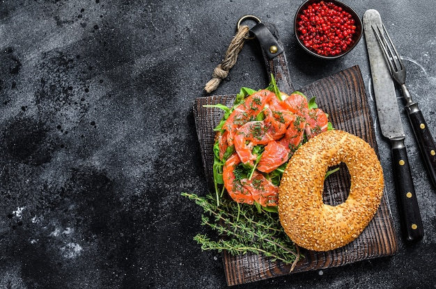 Smoked salmon bagel with soft cheese, arugula on a wooden cutting board. black background. top view. copy space.