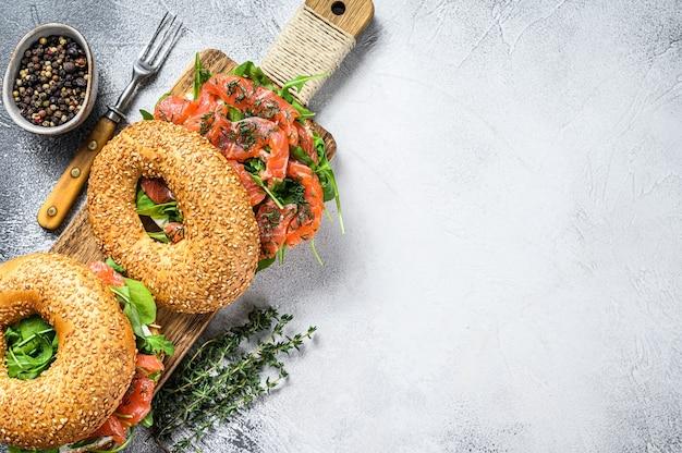 Сэндвич с копчеными бубликами из лосося с мягким сыром и рукколой на разделочной доске. белый фон. вид сверху. скопируйте пространство.