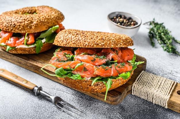 Сэндвич с копчеными бубликами из лосося с мягким сыром и рукколой на разделочной доске. белый фон. вид сверху.