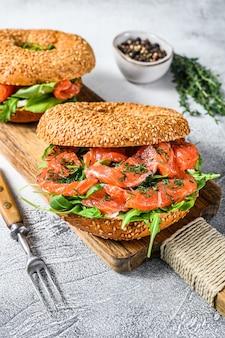 Сэндвич с копчеными бубликами из лосося с мягким сыром и рукколой на разделочной доске.