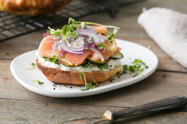 スモークサーモンのベーグルをまな板の上にソフトチーズとマイクログリーンでサンドイッチします。