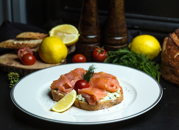 Smoked salmon bruschetta with avocado in cream, and lemon
