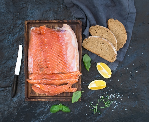 Smoked salmon filet with lemon, fresh herbs and bred on wooden serving board over dark stone backdrop