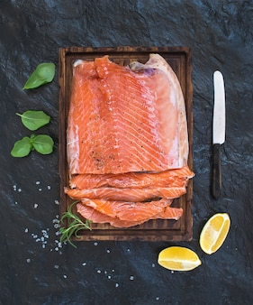 Smoked salmon filet with lemon, fresh herbs and bred on wooden serving board over dark stone wall