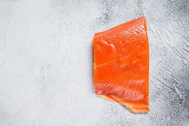 Копченое филе лосося на деревянном столе. белый фон. вид сверху. скопируйте пространство.