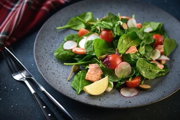 スモークサーモンサラダ。健康的な食事赤い魚、大根、チェリートマトのおいしいサラダ。