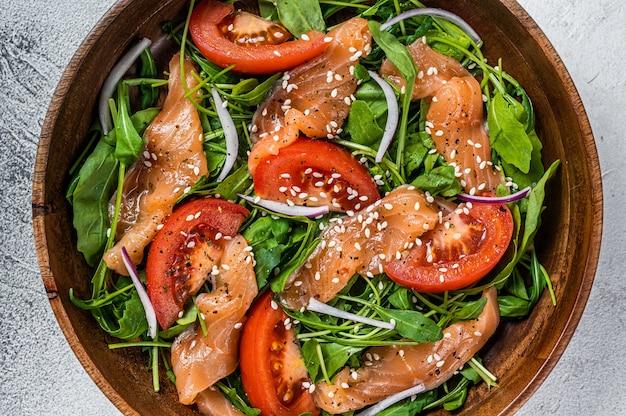 Салат из копченого лосося с рукколой, помидорами и зелеными овощами. белый фон. вид сверху.