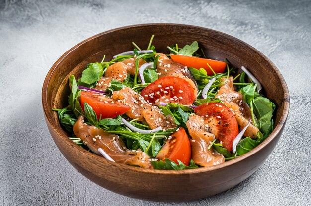 Салат из копченого лосося с рукколой, помидорами и зелеными овощами. белый стол. вид сверху.
