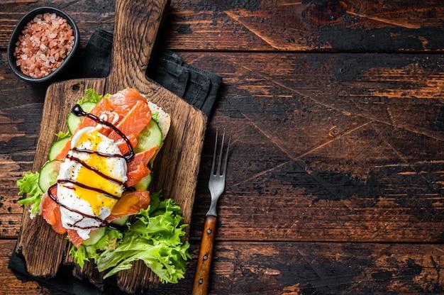 빵에 베네딕트 에그와 아보카도를 곁들인 훈제 연어 샌드위치. 어두운 나무 배경입니다. 평면도. 공간을 복사합니다.