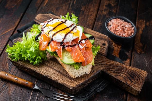 Сэндвич с копченым лососем, яйцом бенедикт и авокадо на хлебе. темный деревянный фон. вид сверху.