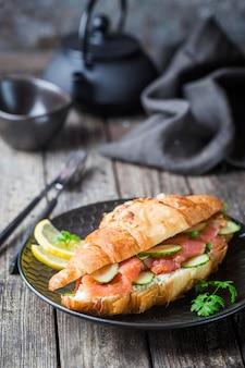 Сэндвич с копченым лососем и свежим сливочным сыром и огурцами на черной тарелке