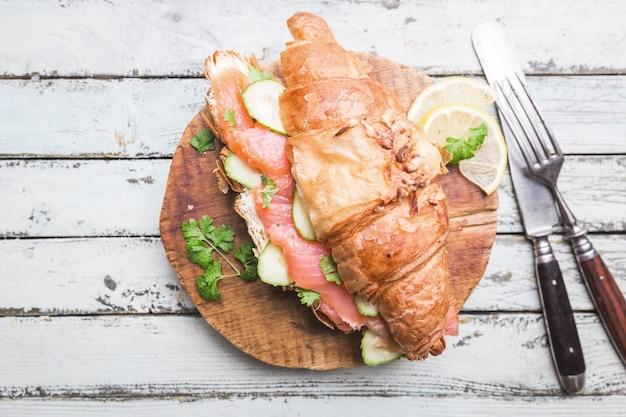 Сэндвич с копченым лососем и свежим сливочным сыром и огурцами на разделочной доске, вид сверху