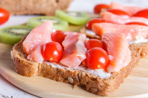 Smoked salmon sandwiches with butter and cherry tomatoes on white wooden background.
