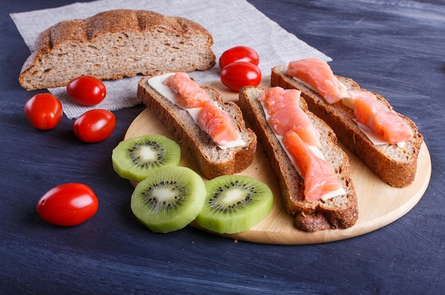 Smoked salmon sandwiches with butter on dark wooden background.