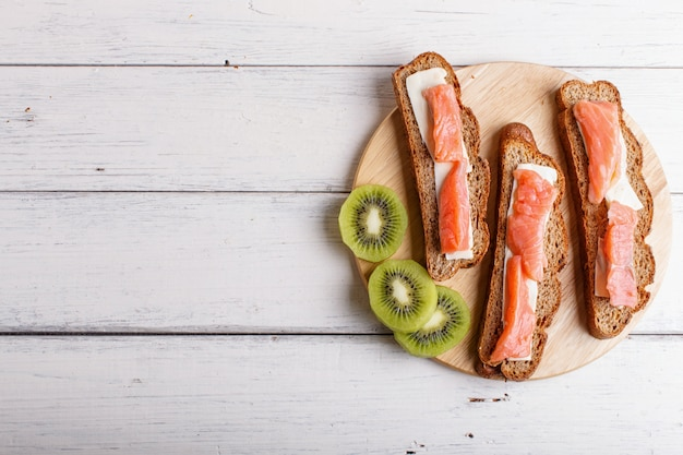 Smoked salmon sandwiches with butter on white wooden background.