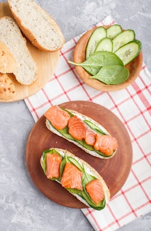 Smoked salmon sandwiches with cucumber and spinach on wooden board on a gray concrete.