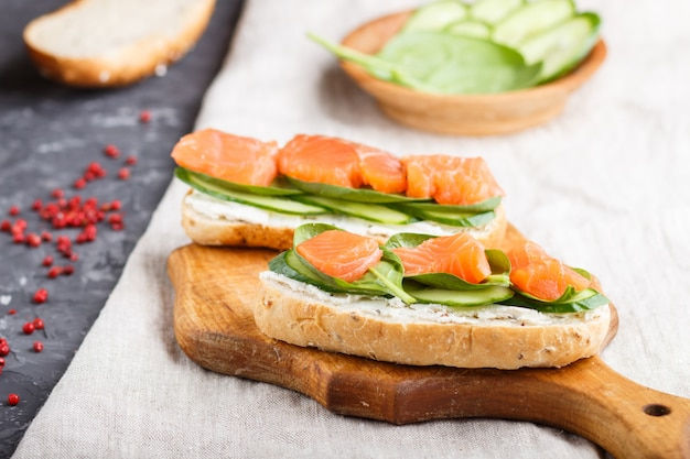Smoked salmon sandwiches with cucumber and spinach on wooden board