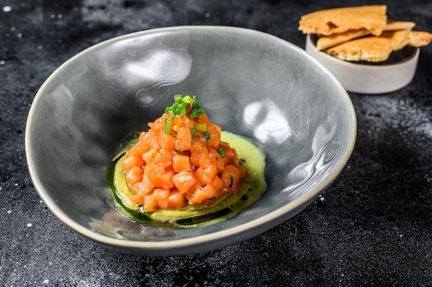 Тартар из копченого лосося и авокадо. черный фон. вид сверху