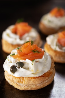 Smoked salmon tartlets snacks with cream cheese on a dark background with copy space.