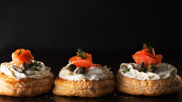 Smoked salmon tartlets snacks with cream cheese on a dark banner