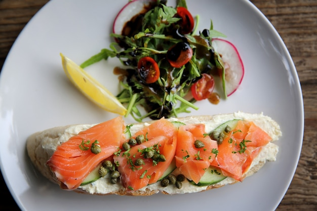 Smoked salmon on toasted bread with cream fresh, lemon and salad