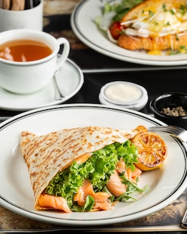 Smoked salmon wrap with lettuce, arugula served with grilled lemon