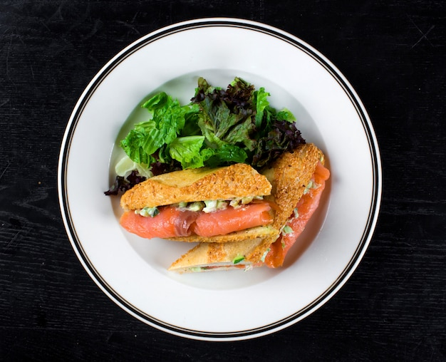Smoked salmon wrapped in bread with side greenery