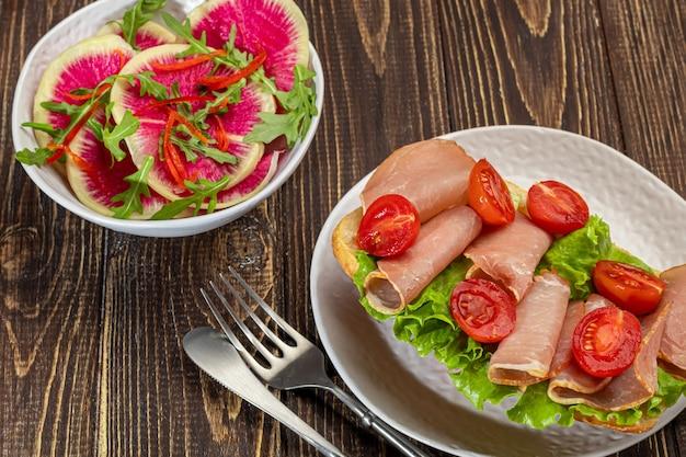 Копченая колбаса и бутерброды со сливочным сыром на тарелке. украшается зеленью укропа. на темном деревянном фоне. скопируйте пространство.