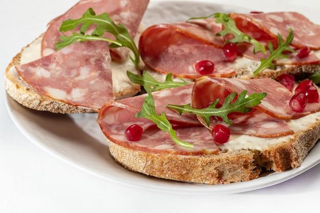 Копченая колбаса и бутерброды со сливочным сыром на тарелке. украшается зеленью укропа. на белом фоне. изолирует. скопируйте пространство.