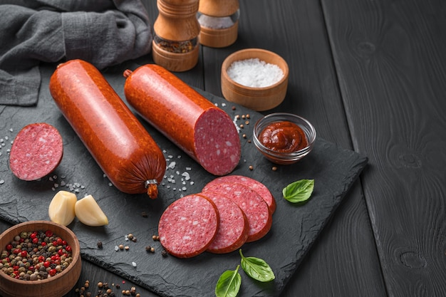 Smoked sausage on a dark background with garlic spices and basil
