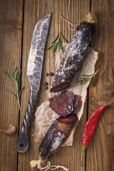 Копченая колбаса из конины на деревянном столе в окружении различных специй
