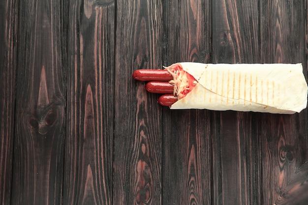 Копченая колбаса в лаваше на темном деревянном фоне. фото с копией пространства.