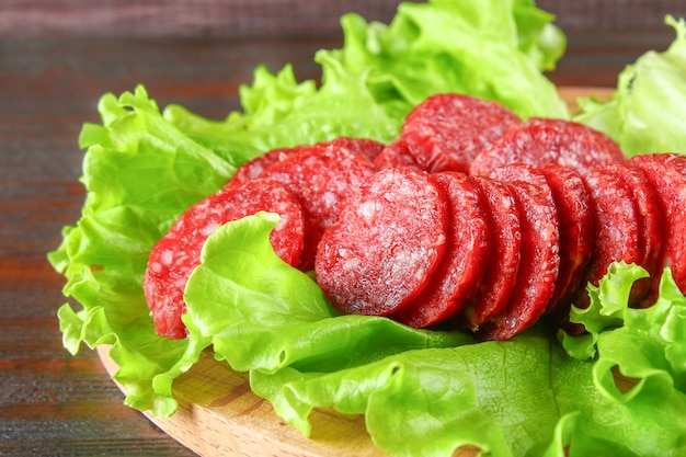 Smoked sausage, salami chopped in slices on a salad on a wooden circular cutting board brown table.