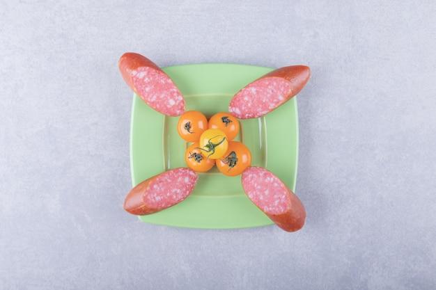 グリーン プレートにスモーク ソーセージとチェリー トマト。