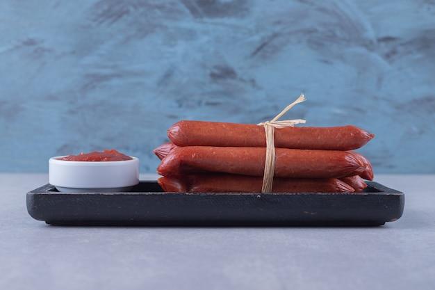 Копченые сосиски и кетчуп на темной тарелке.