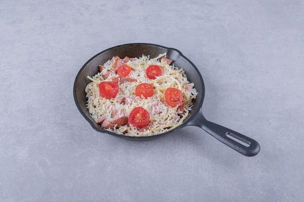 Копченые сосиски и макароны на черной сковороде.