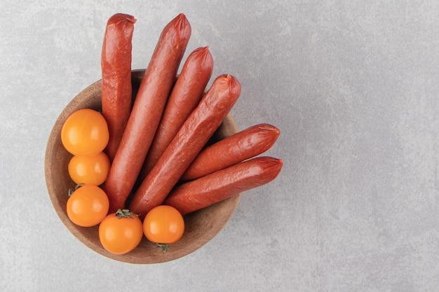 Копченые сосиски и помидоры в деревянной миске.