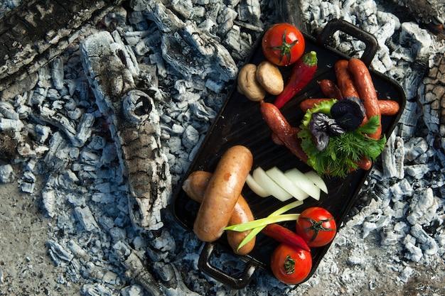 훈제 소시지와 토마토는 숯 위에 놓여 있습니다. 요리는 숯불에 굽고 훈제