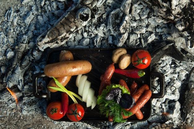 Копченые сосиски и помидоры лежат на углях. блюдо готовят и коптят на углях