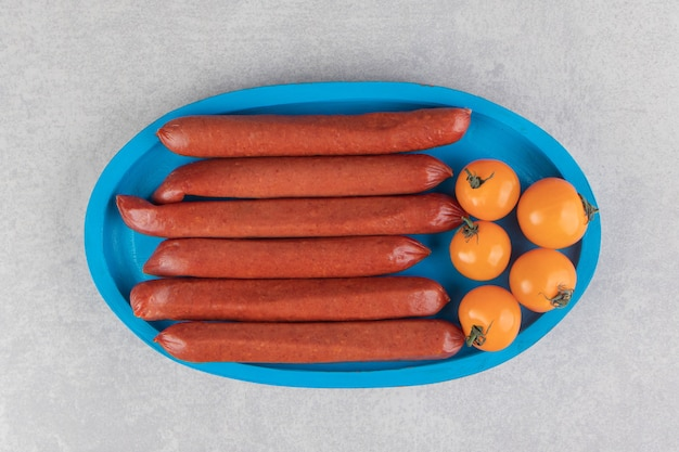 파란색 접시에 소시지와 토마토를 훈제.