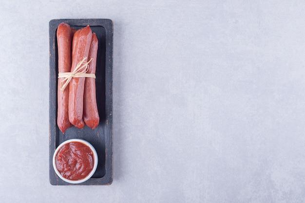 Salsicce affumicate e ketchup su piatto scuro.