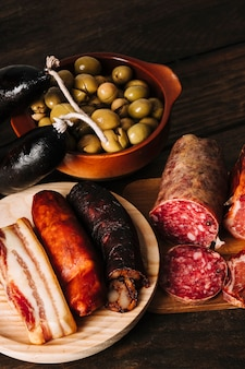 Smoked sausages near pickled olives