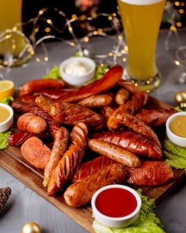 Копченые колбаски подаются с кетчупом, горчицей, майонезом и бокалом пива