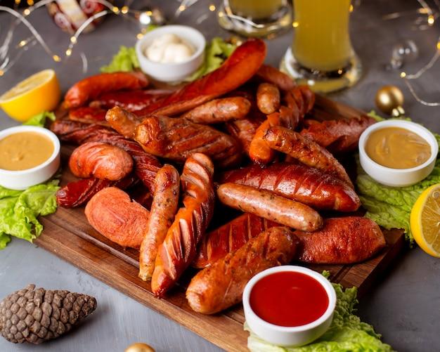 Копченые колбаски с кетчупом, горчицей, майонезом и лимоном