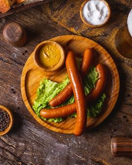 Копченые колбаски с листьями салата и горчицей