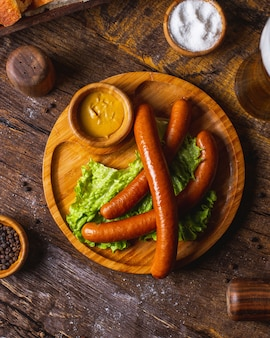Smoked sausages served with lettuce and mustard
