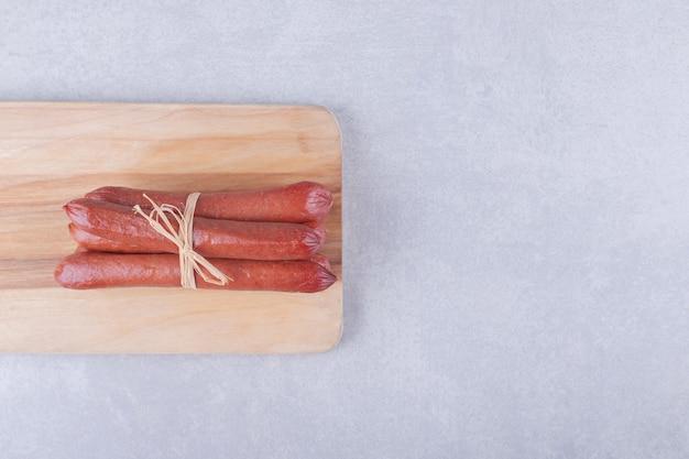 Копченые сосиски, перевязанные веревкой на деревянной доске.