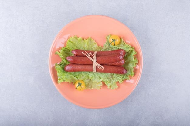 Salsicce affumicate legate con corda sul piatto arancione.