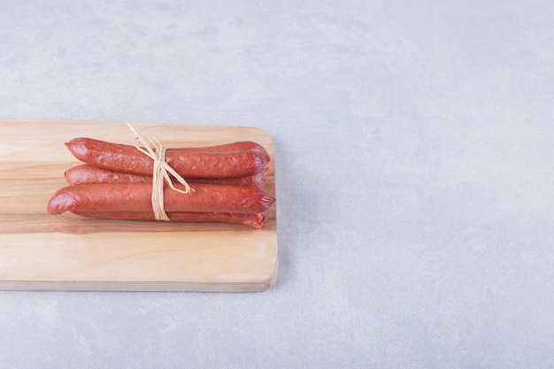 Smoked sausages tied with rope on wooden board.