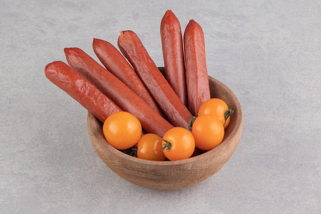 Smoked sausages and tomatoes in wooden bowl.